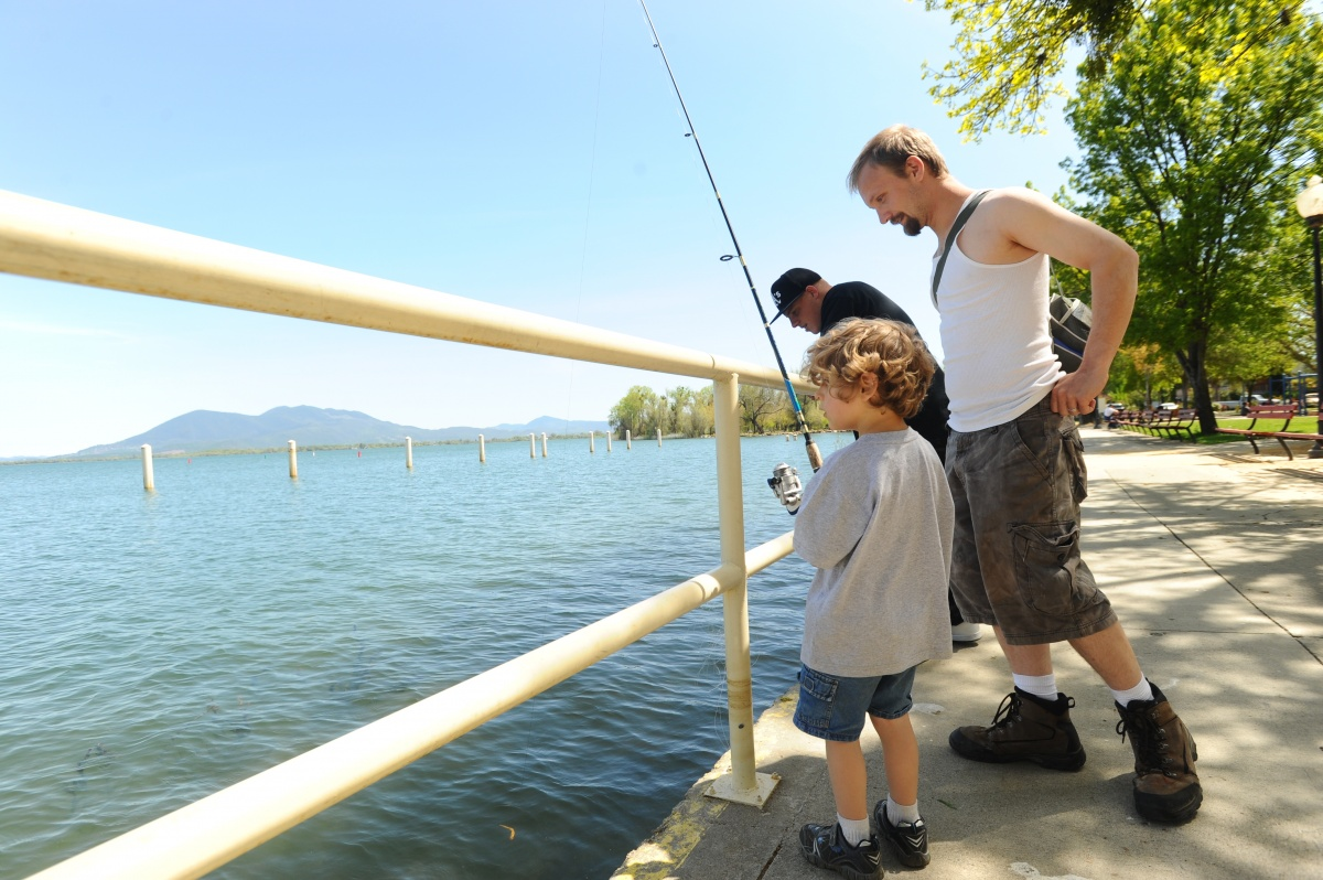 Father fishing at the lake with his kid