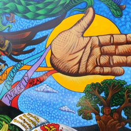 A section of a vivid, painted mural showing an outstretched open hand in front of the sun