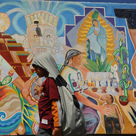 A child walks in front of a mural