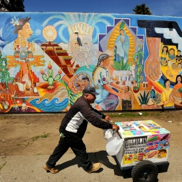A vendor pushes a paletas cart in front of a colorful mural near Fruitvale, California