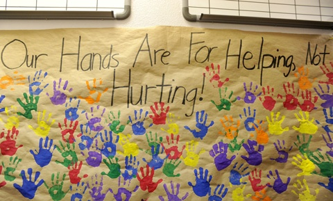 """Text of a banner reads """"Our hands are for helping, not hurting!"""""""