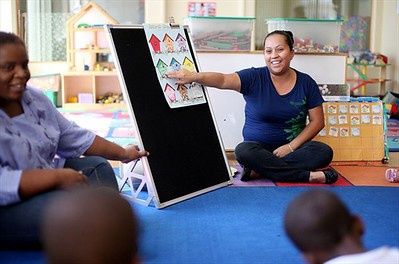 A woman gestures at drawings of houses on a chalkboard, interacting with young students