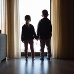 two kids holding hands looking out a window