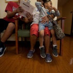 Mo and two kids sitting in a waiting room