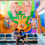 Doctor and patient in front of mural at a community health center