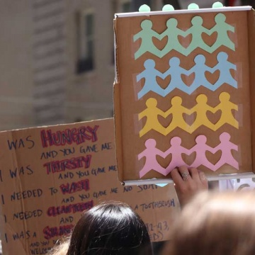 A woman holds a sign up a rally; the sign shows paper cutouts of people