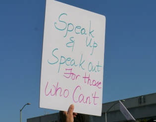 sign that says speak up and speak out for those who can't