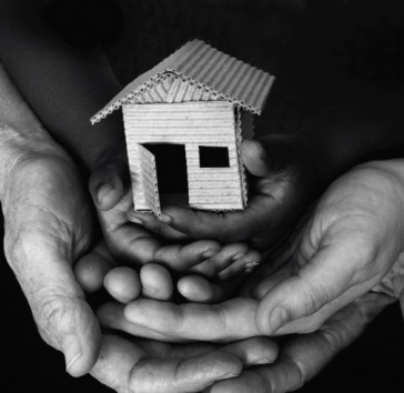 Hands holding a small cardboard house