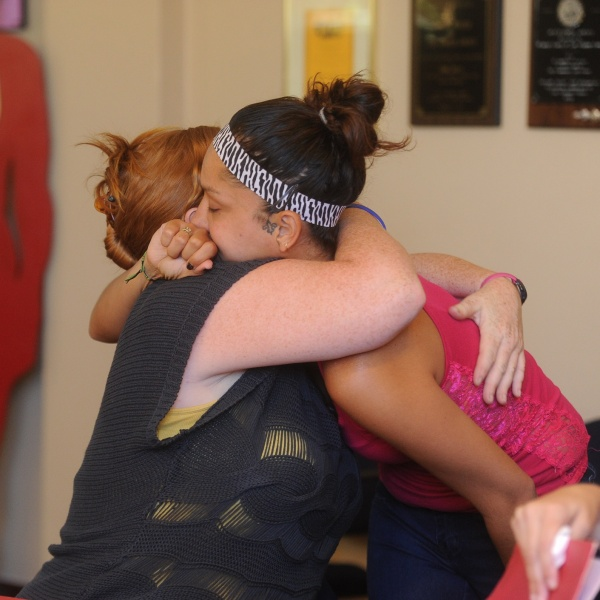 Two survivors of domestic violence hug
